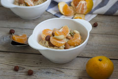 Oatmeal with tangerine and walnuts. Oatmeal with tangerine and walnuts for breakfast, close-up. Selective focus Stock Image