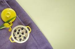 Oatmeal w garnku, muesli z świeżymi czarnymi jagodami i rodzynki, Żółty irys dla dekoracji na purpurze obraz royalty free