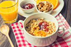 Oatmeal with walnuts, orange peel and jam for breakfast Royalty Free Stock Photo