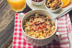 Oatmeal with walnuts, orange peel and jam for breakfast Stock Photography