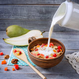 Oatmeal with walnuts and slices of fruit, pouring milk from a ju Royalty Free Stock Image