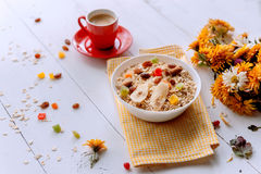 Oatmeal on white background. Oatmeal with nuts and berries. dereennom on white background. beside a cup of coffee and a bouquet of flowers. breakfast concept Stock Images