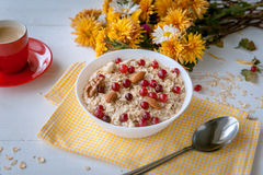 Oatmeal on white background. Oatmeal with nuts and berries. dereennom on white background. beside a cup of coffee and a bouquet of flowers. breakfast concept Royalty Free Stock Photos