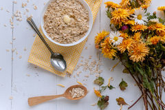 Oatmeal on white background. Oatmeal with nuts and berries. dereennom on white background. beside a cup of coffee and a bouquet of flowers. breakfast concept Royalty Free Stock Images