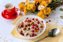 Oatmeal on white background. Oatmeal with nuts and berries. dereennom on white background. beside a cup of coffee and a bouquet of flowers. breakfast concept Royalty Free Stock Photography