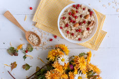 Oatmeal on white background. Oatmeal with nuts and berries. dereennom on white background. beside a cup of coffee and a bouquet of flowers. breakfast concept Royalty Free Stock Image