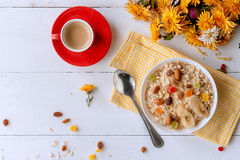 Oatmeal on white background. Oatmeal with nuts and berries. dereennom on white background. beside a cup of coffee and a bouquet of flowers. breakfast concept Royalty Free Stock Photo