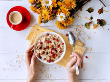 Oatmeal on white background. Oatmeal with nuts and berries. dereennom on white background. beside a cup of coffee and a bouquet of flowers. breakfast concept Stock Image