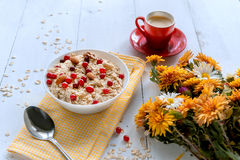 Oatmeal on white background. Oatmeal with nuts and berries. dereennom on white background. beside a cup of coffee and a bouquet of flowers. breakfast concept Stock Photography