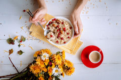 Oatmeal on white background. Oatmeal with nuts and berries. dereennom on white background. beside a cup of coffee and a bouquet of flowers. breakfast concept Stock Photo