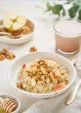 Oatmeal z jabłkiem, dokrętkami, cynamonem, miodem i filiżanką kakao na białym drewnianym lekkim tle, pionowo Zdrowej diety śniada zdjęcie stock