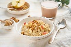 Oatmeal z jabłkiem, orzechami włoskimi i filiżanką kakao na białym drewnianym lekkim tle, Boczny widok Zdrowej diety śniadanie zdjęcia stock