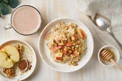 Oatmeal z jabłkiem, orzechami włoskimi i filiżanką kakao na białym drewnianym lekkim tle, Odgórny widok Zdrowej diety śniadanie obrazy stock