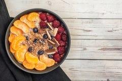 Oatmeal z tangerine, czarnymi jagodami, czekoladą i malinką na lekkim drewnianym stole, Odgórny widok Z kopii przestrzenią zdjęcia royalty free
