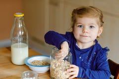 Oatmeals sani del bambino di cibo adorabile della ragazza con latte per il bambino felice sveglio del bambino della prima colazio immagini stock libere da diritti
