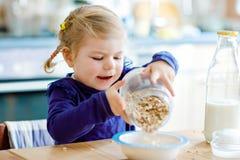 Oatmeals sanos de la consumici?n adorable de la ni?a peque?a con la leche para el ni?o feliz lindo del beb? del desayuno en senta fotografía de archivo