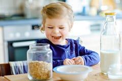 Oatmeals sanos de la consumici?n adorable de la ni?a peque?a con la leche para el ni?o feliz lindo del beb? del desayuno en senta fotos de archivo