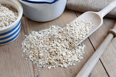 Oats. Porridge Oats, Scoop, Spurtle and Pan on Wooden Kitchen Table stock photography