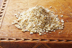 Oats. A heap pf raw rolled oats on an old wooden board royalty free stock images