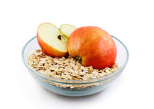 Oats and apple halves in transparent bowl Royalty Free Stock Photos