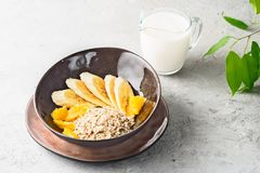 Oats Barley Wheat Rye Corn mix flake proper nutrition diet with pieces banana orange and glass of milk. Concept food healthy breakfast ingredients for recipe Stock Photography