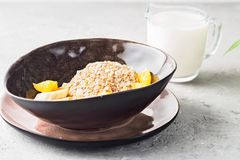 Oats Barley Wheat Rye Corn mix flake proper nutrition diet with pieces banana orange and glass of milk. Concept food healthy breakfast ingredients for recipe Stock Photo