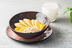 Oats Barley Wheat Rye Corn mix flake proper nutrition diet with pieces banana orange and glass of milk. Concept food healthy breakfast ingredients for recipe Royalty Free Stock Photo