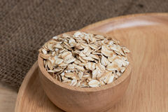 Oats in bowl on wooden plate Royalty Free Stock Photos