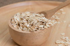 Oats in bowl on wooden plate Stock Images