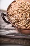 Oats in a copper bowl on a wooden stand closeup Stock Photo
