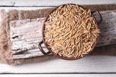 Oats in a copper bowl on a wooden stand Royalty Free Stock Images