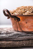 Oats in a copper bowl on a wooden stand on the napkin Stock Images