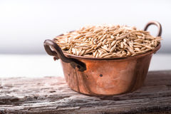 Oats in a copper bowl on a wooden stand side view Stock Image
