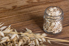 Oats and flakes on a wooden table. Detail of organic oat and jar with rolled oats on brown vintage background royalty free stock images