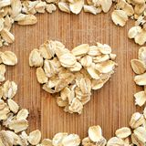Oats in heart shape arranged on wood grain in square format for social media, banners and backgrounds. stock photo