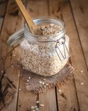 Oats in a jar, on wooden background stock photography