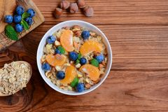 Oats porridge without sugar. Porridge with fresh tangerines, blueberries and hazelnuts in a white bowl and on a wooden background. Healthy porridge recipe for Stock Photo