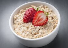 Oats. Pot with oats, milk and strawberries to use in product packaging royalty free stock photos