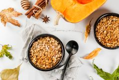 Oats and pumpkin crumble. Dietary autumn pastries, breakfast. Crumble pumpkin pie, maple syrup and oatmeal flakes, in plate saucers, on a white marble table Stock Photography