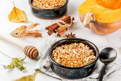 Oats and pumpkin crumble. Dietary autumn pastries, breakfast. Crumble pumpkin pie, maple syrup and oatmeal flakes, in plate saucers, on a white marble table Royalty Free Stock Images