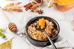 Oats and pumpkin crumble. Dietary autumn pastries, breakfast. Crumble pumpkin pie, maple syrup and oatmeal flakes, in plate saucers, on a white marble table Royalty Free Stock Image