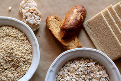Oats and rice in a bowl. Rice cakes and bread in background. Foods high in carbohydrate. Stock Photo