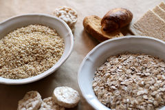 Oats and rice in a bowl. Rice cakes and bread in background. Foods high in carbohydrate. Royalty Free Stock Photo