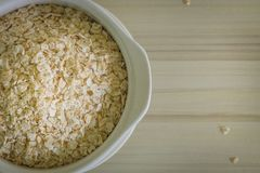 The oats rice in white bowl on top table wood worm tone image. Oats rice in white bowl on top table wood worm tone image stock photography