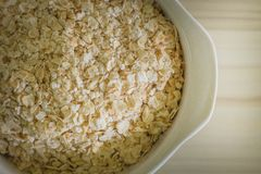 The oats rice in white bowl on top table wood worm tone image. Oats rice in white bowl on top table wood worm tone image stock photos