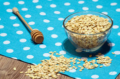 Oats scattered on the table, poured in a bowl and spoon for honey Royalty Free Stock Photos
