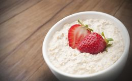 Oats and strawberries. Pot with oats, milk and strawberries to use in product packaging stock image