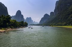 Oats with tourists cruising in the Li River with the tall limestone peaks in the background near Yangshuo in China Royalty Free Stock Image