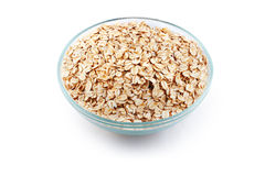 Oats in transparent bowl isolated on white Stock Photos