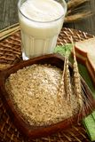 Oats in wooden bowl with  glass of milk on wooden Stock Photos